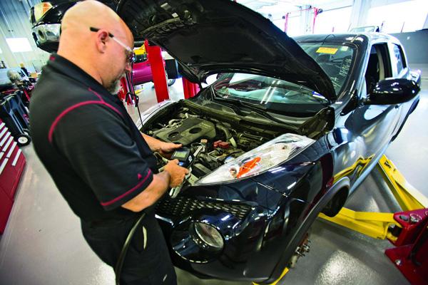 芬顿日产4S店的技师Danny Johnson为客户检查车辆