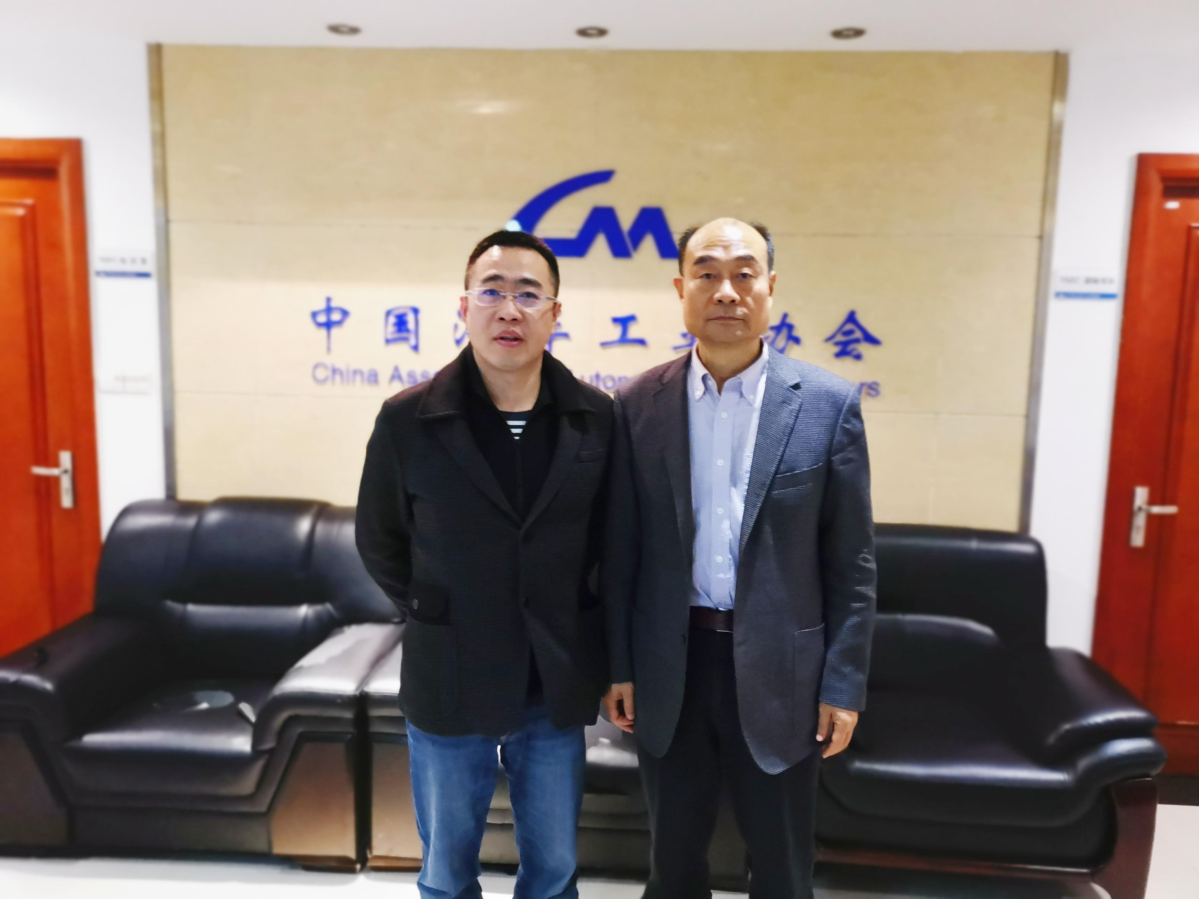 车云网、电动邦创始人程李(左)与中国汽车工业协会副秘书长师建华(右)合影