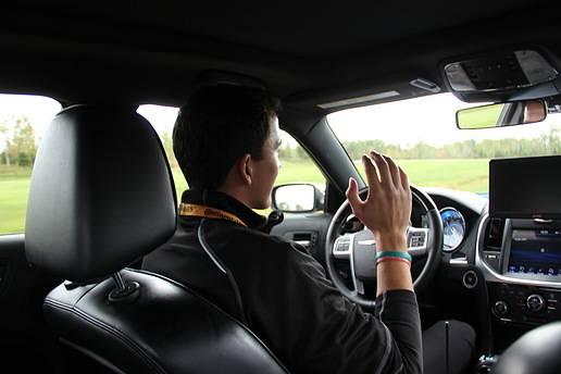 """大陆集团工程师Steffen Hartmann坐在大陆""""巡航司机""""演示车中,双手并没有握着方向盘,即使此时车辆正在进行高速行驶。"""