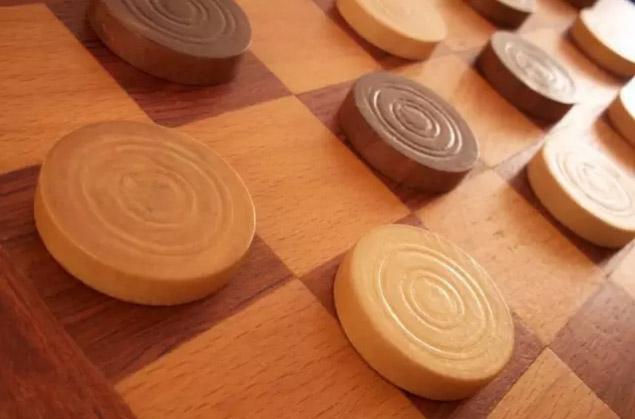 成王(King me):能下国际跳棋的程序是早期人工智能的一个典型应用,在二十世纪五十年代曾掀起一阵风潮。(译者注:国际跳棋棋子到达底线位置后,可以成王,成王棋子可以向后移动)。