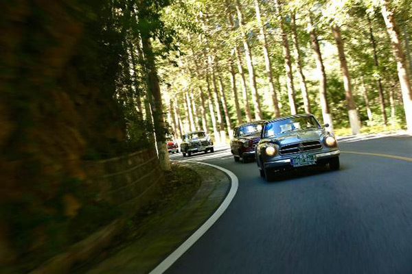 老爷车车队行驶于拉力赛蜿蜒的山路段