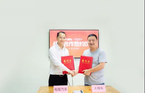 电咖汽车CMO向东平(左)与大搜车创始人兼CEO姚军红(右)交换签约文件